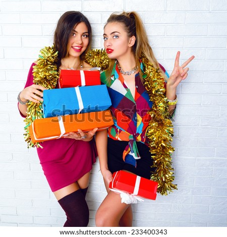 Beautiful happy smiling funny best friends sisters, holding party gifts and presents. wearing trendy clothes and masquerade golden tinsel. White urban brick wall background. Positive holiday mood. - stock photo
