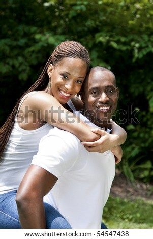 Beautiful happy smiling laughing young African American couple piggyback playing in the park, woman hugging man, wearing white shirts and blue jeans. - stock photo