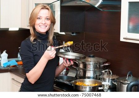 Beautiful happy smiling woman in kitchen interior cooking - stock photo