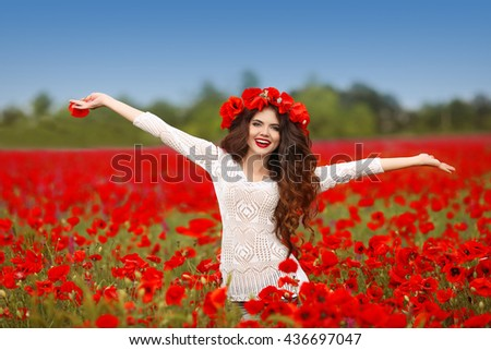 Beautiful happy smiling woman open arms in red poppy field nature background. Attractive brunette young girl model with curly hair and makeup laughing at camera - stock photo