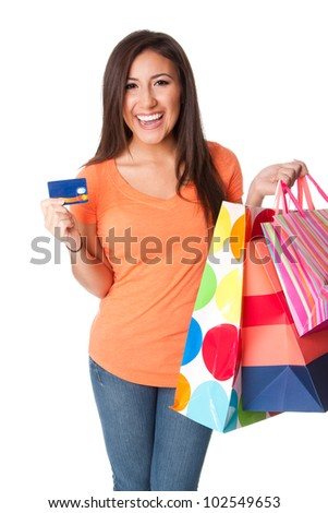 Beautiful Happy smiling young woman on shopping spree with credit card lastic money carrying colorful bags with merchandise presents, isolated. - stock photo