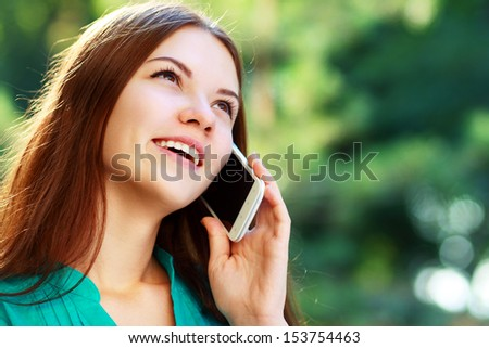 beautiful happy smiling young woman using mobile, sitting in park, smiling - stock photo