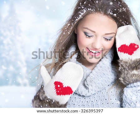 Beautiful happy smiling young woman wearing winter gloves covered with snow flakes. Christmas portrait concept. Winter landscape background - stock photo