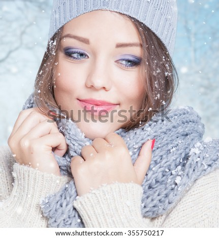 Beautiful happy smiling young woman wearing winter hat covered with snow flakes. Christmas portrait concept. Winter landscape background - stock photo