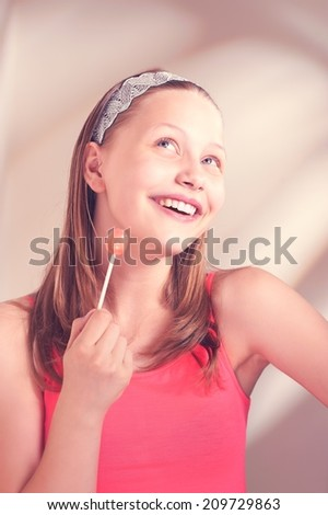 Beautiful happy teen girl smiling and holding lollipop - stock photo