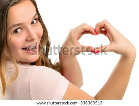 Beautiful happy teenage girl shows gesture heart. - stock photo