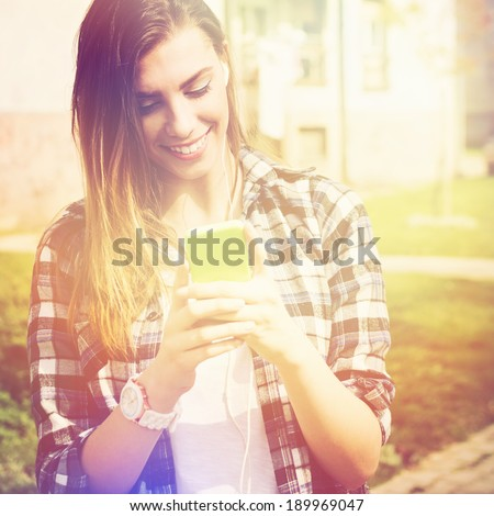Beautiful happy teenage girl with phone texting. Caucasian brunette young woman smiling reading text message on her phone.  - stock photo