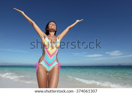 Beautiful happy woman in bikni with raised hands on tropical beach - stock photo