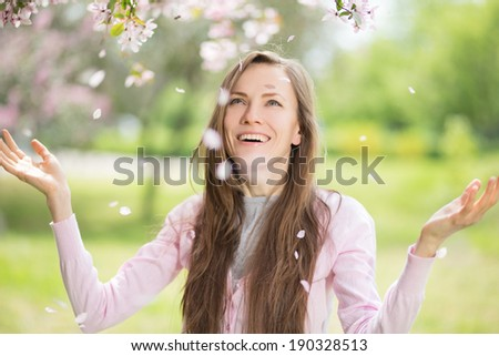 Beautiful happy woman in spring park enjoying the nature. motion, focus on mouth - stock photo