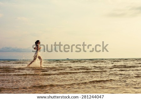 Beautiful happy woman in white dress running on the sea on sunset, freedom and travel abstract concept - stock photo