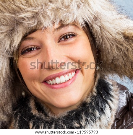 Beautiful happy woman in winter clothes with a bright smile. Square studio shot against a light blue background as a wintry close up portrait - stock photo