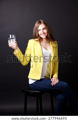Beautiful happy woman raising her glass of water - stock photo