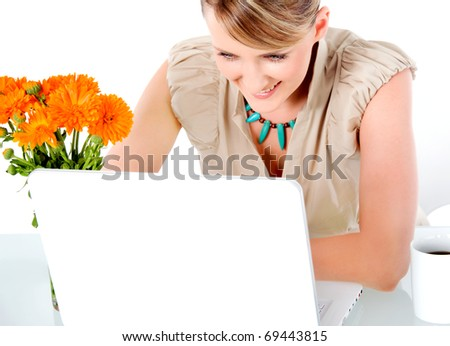 Beautiful happy woman sitting behind desk with laptop, looking at screen - stock photo