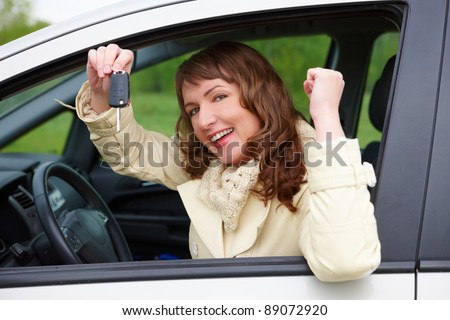 Beautiful happy woman sitting in a car and showing keys out the window - stock photo