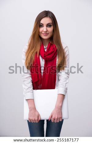 Beautiful happy woman standing with laptop over gray background - stock photo