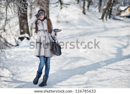 Beautiful happy woman walking in the winter forest - stock photo