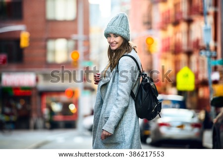 Beautiful happy woman walking on the city street wearing casual grey coat and hat with a bag - stock photo