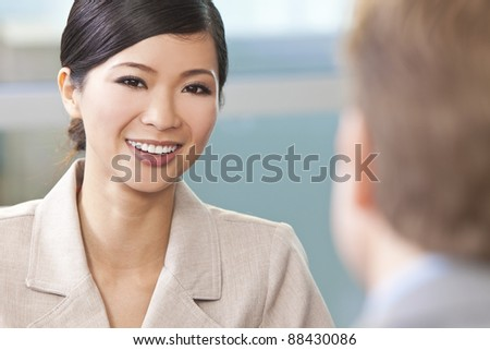 Beautiful happy young Asian Chinese woman or businesswoman in smart business suit - stock photo