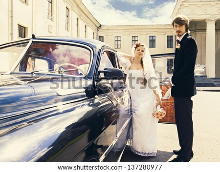 Beautiful happy young bride and groom standing near a retro auto - stock photo