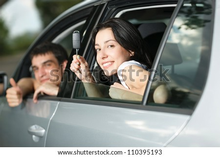 Beautiful happy young couple showing the car keys sitting in new car - stock photo