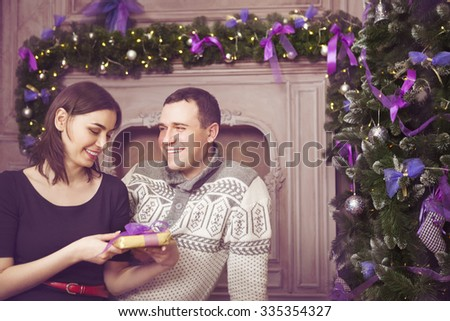 Beautiful happy young couple with present near christmas tree - stock photo
