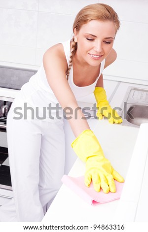beautiful happy young housewife cleaning the furniture in the kitchen at home - stock photo