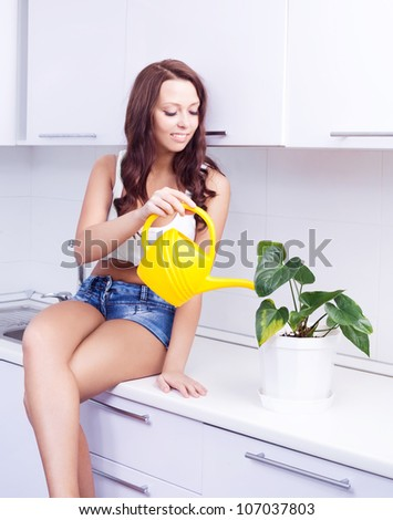 beautiful happy young housewife watering the flowers in pots  in the kitchen at home - stock photo