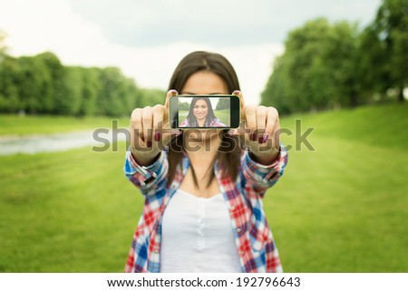 Beautiful happy young mixed race woman taking a selfie photo with smart phone outdoors in park on summer day. Modern millennial youth lifestyle and travel concept. - stock photo