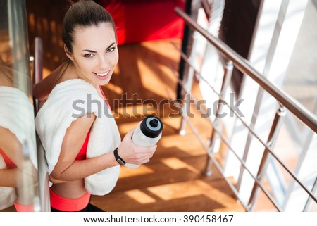 Beautiful happy young sportswoman with white towel drinking water in gym - stock photo