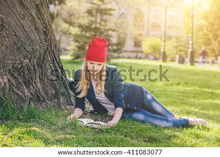 Beautiful, happy young student girl in red hat holding book lie down on green grass under the tree near the campus, university, school, education, pensive. Summer, spring green park, bright sunshine - stock photo