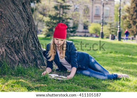Beautiful, happy young student girl in red hat holding book lie down on green grass under the tree near the campus, university, school, education, pensive. Summer, spring green park - stock photo