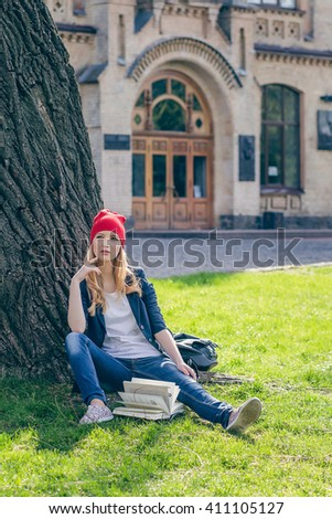 Beautiful, happy young student girl in red hat holding book sitting on green grass under the tree near the campus, university, school, education. Summer, spring green park - stock photo