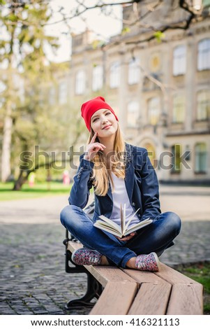 Beautiful, happy young student girl in red hat holding book sitting on the bench near the campus, university, school, education. Summer, spring green park pensive look - stock photo