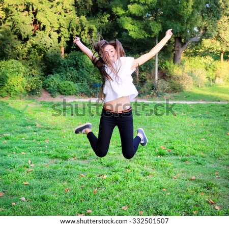 Beautiful happy young teen girl jumping high in the park - stock photo