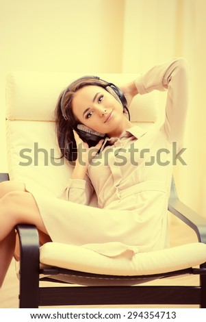 Beautiful happy young woman at home in a comfortable chair. - stock photo