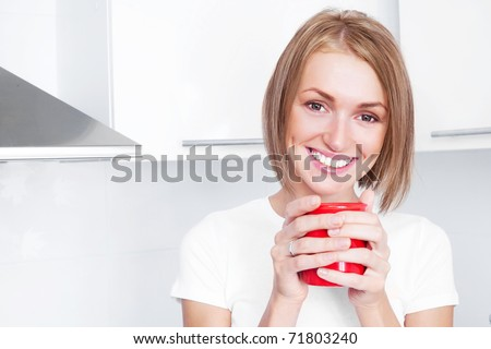 beautiful happy young woman drinking coffee at home in the morning - stock photo