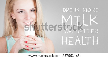 Beautiful happy young woman drinking milk - isolated on old grey wall background with DRINK MILK FOR BETTER HEALTH text - stock photo