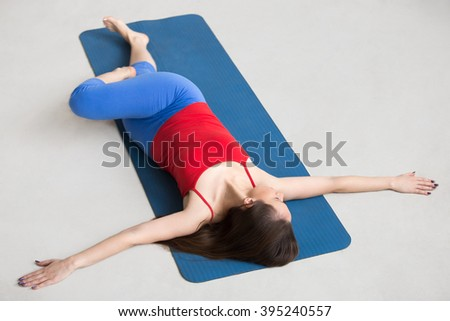 Beautiful happy young woman in bright colorful sportswear working out indoors on blue mat. Girl lying in Reclining Spinal Twist, Jathara Parivartanasana, resting after practice, full length, top view - stock photo