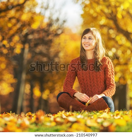 Beautiful happy young woman in the autumn park. Joyful woman is having fun outdoors in a bright yellow trees. Colorful fall concept. - stock photo