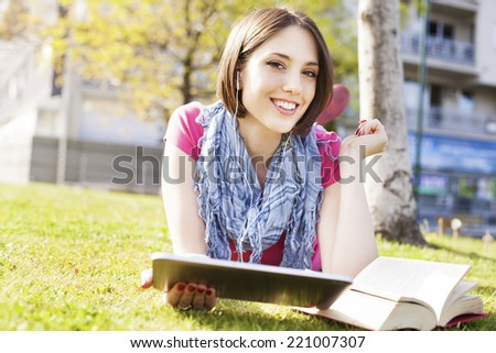 Beautiful happy young woman lying on grass, enjoy sunny day and listening music with headphones and using digital tablet while reading book.  - stock photo