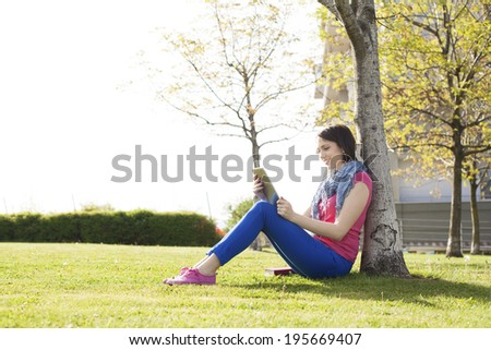 Beautiful happy young woman sitting on grass, enjoy sunny day and listening music with headphones while reading book.  - stock photo