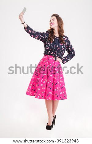 Beautiful happy young woman standing and taking selfie with smartphone over white background - stock photo