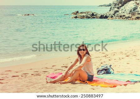 Beautiful happy young woman wearing sunglasses smiling at camera while sitting on sand beach on summer holidays travel in Spain - stock photo