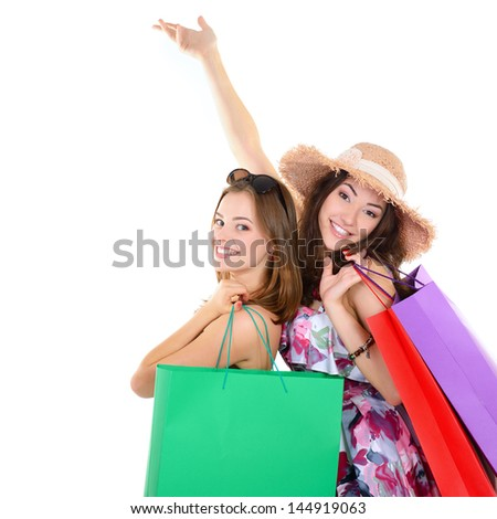 Beautiful happy young women with colored shopping sale bags in summer clothes pointing with hands up into the copyspace over white - stock photo