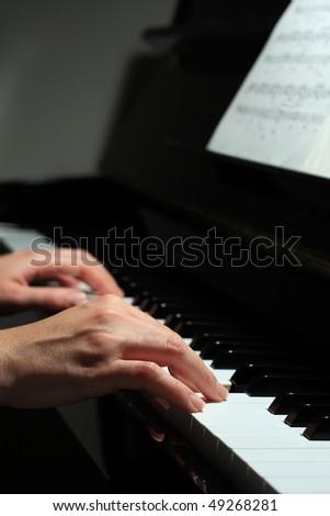 Beautiful, harmonious detail of a black piano - stock photo