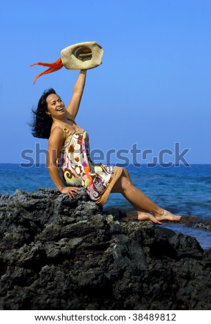 Beautiful hawaiian woman sits on rocky beach on the Kohala Coast and waves a welcome.  She is wearing a sundress and waving a straw hat with colorful scarf. - stock photo