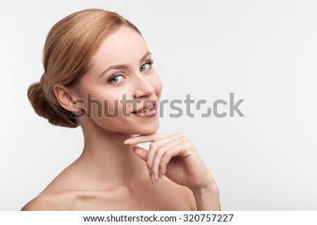 Beautiful healthy blond woman is posing with naked shoulders. She is standing and smiling. The lady is looking at camera happily and touching face. Isolated and copy space in right side - stock photo