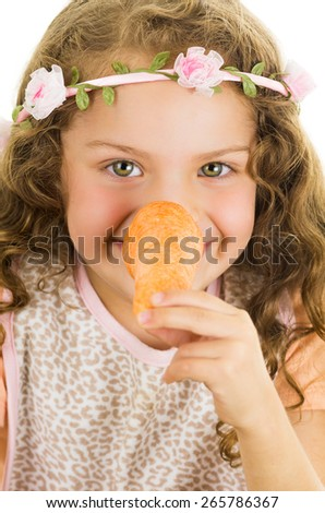 Beautiful healthy little curly girl enjoying playing with a carrot in front of her nose isolated on white - stock photo