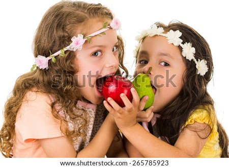 Beautiful healthy little girls eating delicious fresh fruits isolated on white - stock photo