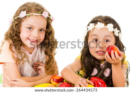 Beautiful healthy little girls holding delicious fresh fruits and vegetables isolated on white - stock photo